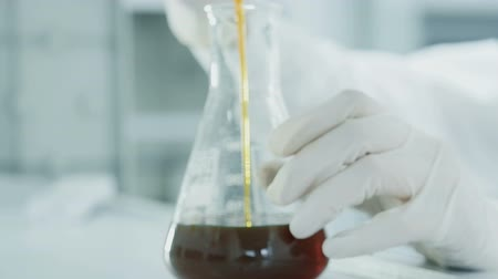 oil drop : Laboratory concept, person close up dropping solute by measure to glass slow motion. The process of making cosmetic or scrutiny expertise of petrol. The scientist chemist testing the chemical material Stock Footage