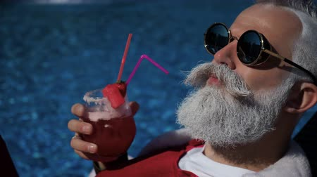 satysfakcja : Happiness and satisfaction at the tropical new year. Crazy cheerful traveler chilling on sunbathing bad in santa costume, tanning on the sun, drinking alcohol with straw near with hotel swimming pool