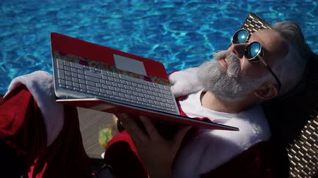 piada : Merry Christmas comic concept in the summertime country. Funny Santa sunbathing on the bad near with swimming pool and use laptop like a reflection. Background of offline vacation without technology
