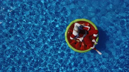 приехать : Aerial view: Santa lie on the watermelon inflatable ring and calling to come makes a hand gesture. Concept of satisfaction and xmas vacation. Cheerful man celebrate life, summertime and happiness Стоковые видеозаписи