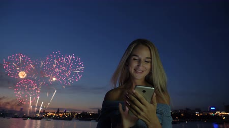 firecracker : Smiling adult girl with smartphone, at background exploding fireworks. Festival concept, blonde lady chatting at telephone and congratulates online with new year at holiday standing at town seaside Stock Footage
