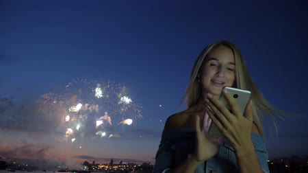 felicitação : Smiling adult girl with smartphone, at background exploding fireworks. Festival concept, blonde lady chatting at telephone and congratulates online with new year at holiday standing at town seaside Stock Footage
