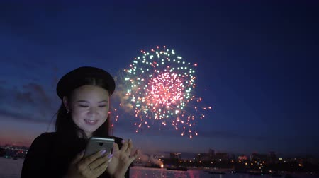 набережная : Young pretty woman in love talking in chat on line with a boyfriend standing at the downtown seafront and looking at cellphone. At background exploding new year fireworks. Travel and holiday concept Стоковые видеозаписи