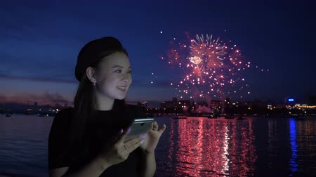 набережная : Happy young woman celebrate the New Year at vacation and texting a message to friends by the cellphone using wireless standing on the riverside. The fireworks colored lights reflections on the water Стоковые видеозаписи