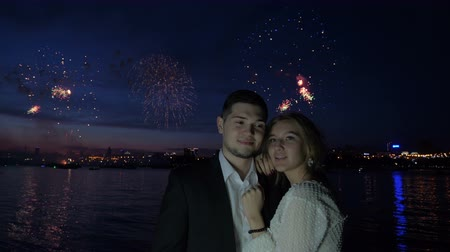 набережная : Girlfriend and boyfriend on the evening date. Beautiful scenery view of colored skyline in fireworks flashes reflected on the lake. Happy couple on festive. Art, love, tenderness entertainment concept Стоковые видеозаписи