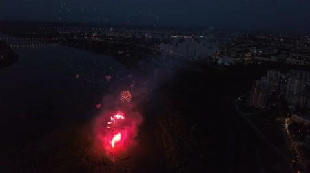 искра : Amazing scenic footage of firecrackers above the modern illumination city at festive for New Year or Christmas or Independence day. Colorful firecracker moving up and bursting shiny bright in the sky