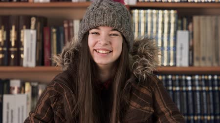 knihkupectví : Face portrait teenager in winter clothes in bookstore, positivity concept. Creative lifestyle model shooting. Adult girl with bookshelves at background. Beautiful bookworm in college class room