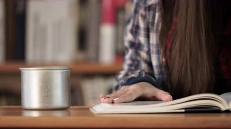 livraria : Closeup isolated education concept. Wooden table with open book and female hands, bookshelf at background. Girl drinking something and concentration to textbook in creative workplace, searching ideas