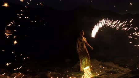 actrice : Scenery juggling with sparkling flame. Art event, presentation traveling summer season. Beautiful model standing on the improvised stage at beachline and enjoyment turning flashing sparkles torches