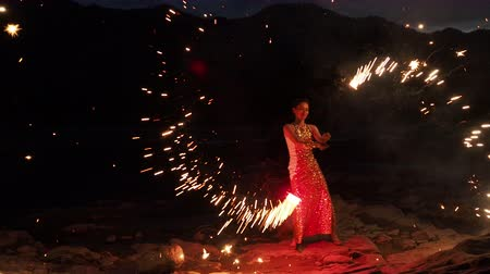improvised : Scenery juggling with sparkling flame. Art event, presentation traveling summer season. Beautiful model standing on the improvised stage at beachline and enjoyment turning flashing sparkles torches