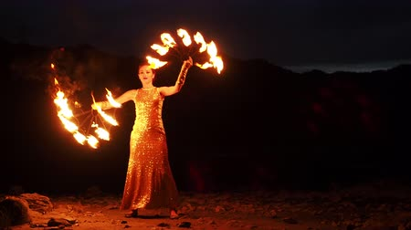 színésznő : Scenery fireshow at open air. Attractive juggler rotate flamy fans on the darkness. Professional stylish entertaining concept. Happy smiling firegirl portrait with flaming sparkling sticks in costume