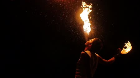 diffuse : Enjoyment concept entertaining tourists. Professional actor showing flamy spectacle. Young man standing and diffuse in air flaming splash from mouth. Riskily workmanship presentation at darkness area