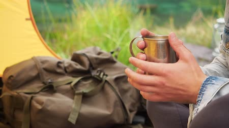 tea bag : Close up camping concept. Man hands keep the iron mug and enjoying warmed by hot drink in spring cold morning outdoor. Details of backpacking travel and natural wild scene pov from yellow tent Stock Footage
