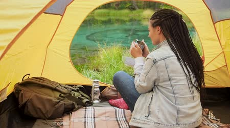 ribeiro : Back view woman backpacker resting at morning outdoor sitting in yellow tent. inspiration and happiness travelling recreational background. Adult girl enjoy landscape scene to the river and forest pov