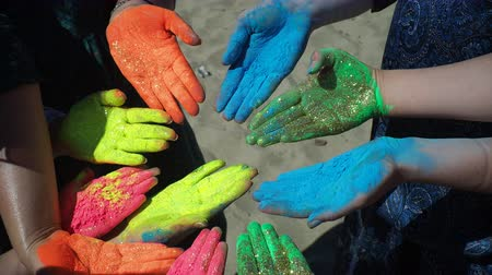 hinduizmus : The festival of colors Holi. Hands painted in mixed colors close up. Male and female persons sitting on beachline and doing hindian ritual. Scereny colorful picture of peace and art, summer enjoyment