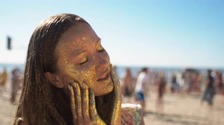 sensibilidad : Adult trendy teenage girl with covered face in gold glitter posing to camera on the beach. Sunny weather, the suns rays are played on sparkles. Art concept, modeling and recreation at summertime