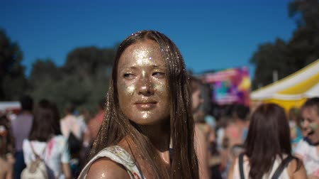 santo : Young teenage covered in gold glitter smiling and looking at camera. At background many people are enjoying and having fun. Sun is shining and sparkling on the face of female person. Fashion concept