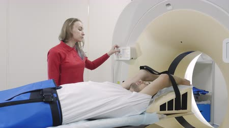 tomograph : CT-scan moving with lying man for diagnostics any health problem and detect disease. Medicine technology equipment is a computer tomography scanning patient. Doctor push a button at control panel Stock Footage