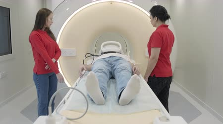 излучение : Woman with student doing MRI scanning for patient with oncology diagnosis lying there in in innovation lab. Machine moving out and doctor take off the headphones from the man head after procedure