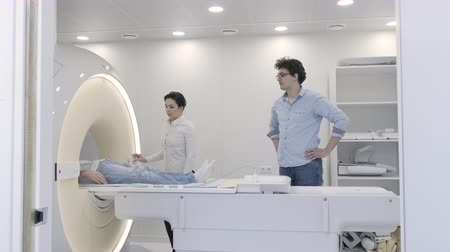 tomograph : Professional woman operator control the MRI scanner during diagnostics process. Doctor waiting results at tomography procedure in hospital radiotherapy room while patient moving inside the tube