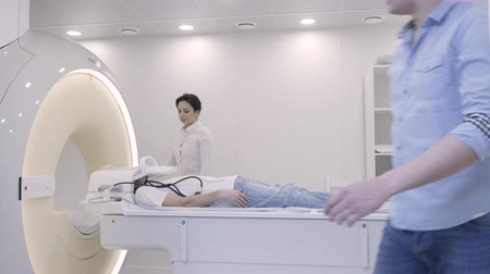 tomograph : Female doctor controlling the MRI diagnostics for patient with head brain oncology. Woman switch on and moving the lying man inside the tube of magnetic resonance imaging scanner. Medicine technology Stock Footage
