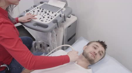 computed : Man lying during undergoing ultrasound diagnostic for thyroid. Ultrasonography doctor using researcher scanner at ratient neck. Female hand holding instrument and carefully checking a problem area