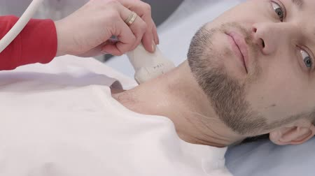 sonography : Male patient undergoing ultrasound diagnostic procedure for neck. Ultrasonography doctor using equipment for give a diagnose and write a treatment. Man lying during the process in sterile bed