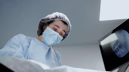 competence : Female surgeon doctor face at operation in hospital room close up. Adult woman at surgery treatment in protective clothes operate the patient with surgical tools and control process at display