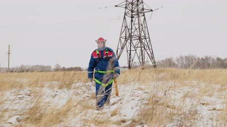 монтаж : Tired repair man walking on the winter field after service electric station. Electrician worker in safety overalls and helmet on the power line construct the voltage wires on the tower on background Стоковые видеозаписи