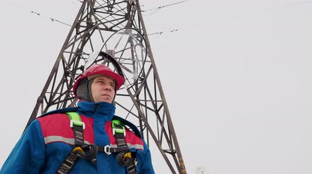 монтаж : Electrician man standing on the power line at snow field and open helmet for breathe the winter air. Electrical station service. Face of male person repair the voltage wires. Danger job outdoor