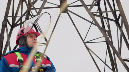 lineman : Face portrait of caucasian adult electrician worker standing on electrical tower background. Man in overalls and helmet working on electricity station at field. Profession in electric infrastructure