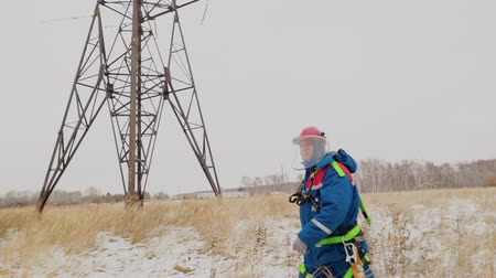 odchodu : Professional electrician in overalls and helmet hurry going repair the voltage wires on the power line. Man working at electric generator station and service electrical pillar on the snow white field