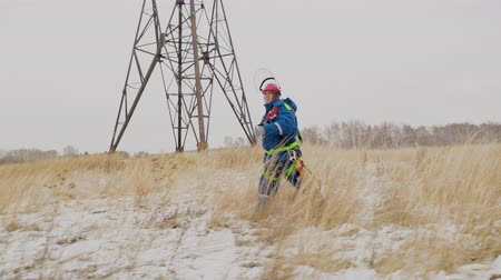 монтаж : Electrician going repair the wires at power line on the wheat field in snow. Adult caucasian man in helmet working at electrical station and service industrial electricity generator on background Стоковые видеозаписи