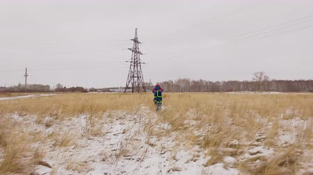 enviroment : Electrician engineer going to the electric line on the snow field. Quadcopter scene: man in safety clothes service the electrical station, repair voltage wires and electricity system on the winter Stock Footage