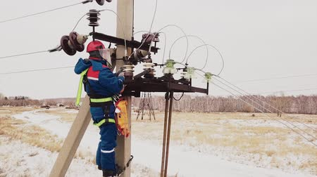 emel : Repairman working at power line with voltage wires on the electrical station. Electrician service the steel cable on tower in safety helmet. Electricity engineering and mounting at pillar on the field Stock mozgókép