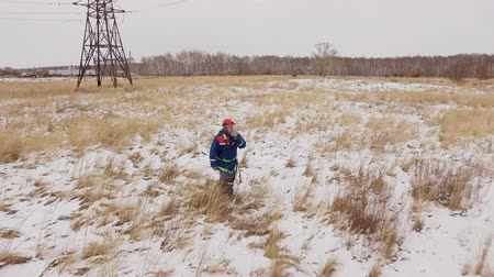 enviroment : Electrician man going on the snow field at electrical station with electric tower at background. Drone view: lineman finish electricity repair of voltage wires and mounting energy line at winter Stock Footage