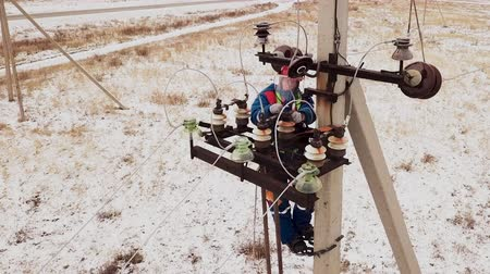lineman : Electrician repairman working on tower at the electric station in safety protection wear. Man repair the power generator on the field using equipment. Electrical service and mounting on the pole