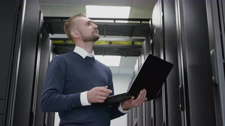 Man holding laptop and do diagnostic of datacenter in server room. Engineer standing in corridor and working with cyberspace system and hardware database. Networking administrator service a big data Stock Footage