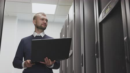 IT engineer walking and control server room of datacenter holding laptop and looking with emotion try to find a problem. Man working with hardware and database, diagnostic maintenance routers Stock Footage