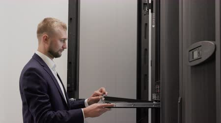 Server engineer working in data center room using laptop for install software. Scene of support business hosting cloud and hardware routers. Technician administrator diagnostic internet system