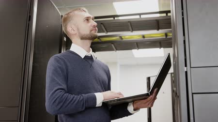 Serious caucasian system administrator holding laptop standing before server rack. Professional engineer working in hosting room corridor. Man diagnostic and support datacenter process using notebook