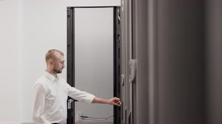 IT engineer open server rack and using laptop for support data center slow motion. Man working in mining farm room with digital storage system and internet cloud technology. Networking concept Stock Footage