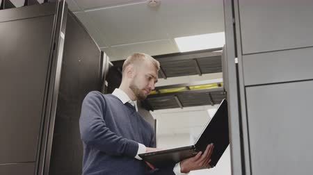 IT engineer working with laptop holding in hand standing before server rack and support data center system. Administrator diagnostic digital storage in corridor with routers. Networking infrastructure