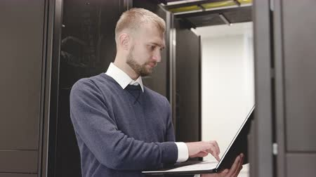 System administrator controlling server rack in room typing at laptop close up. IT programmer working in datacenter with business cyberspace internet technology and hosting security information