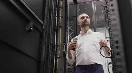Man opening server rack of hosting system in big data center for support software using phone. IT engineer controlling routers and do diagnostics for search problems in cloud security technology Stock Footage