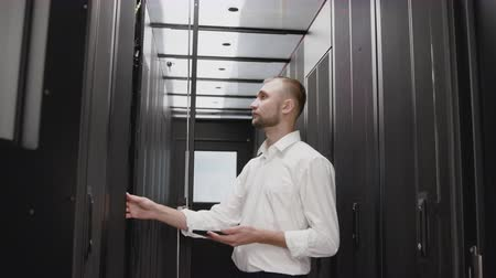 Serious system administrator open server rack for diagnostic with smartphone. IT engineer working in business datacenter storage with information technology database. Occupation and workplace