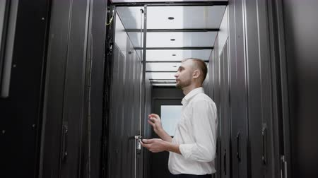 Caucasian man open server rack and checking data center slow motion. Serious system administrator looking to mining farm and diagnostic cloud infrastructure standing before the modern datacenter