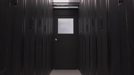 Dark corridor in server room of data center with cloud digital storage. Mining farm and internet information technology concept, no people around. Computer routers in racks on the rows isolated