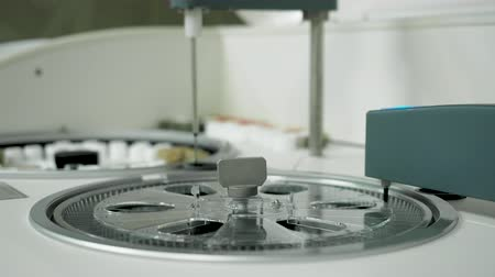 Modern automated robot research biochemical blood test in lab. Centrifuge analyzer rotating and testing bio material in tubes. Medical examine technology device close up, healthcare concept, no people