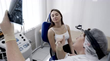 Healthcare and treatment concept. Young woman patient in clinic and doctor with x-ray image diagnoses disease in slow motion. Visit otolaryngologist, survey breath and respiratory system in hospital. Stock Footage